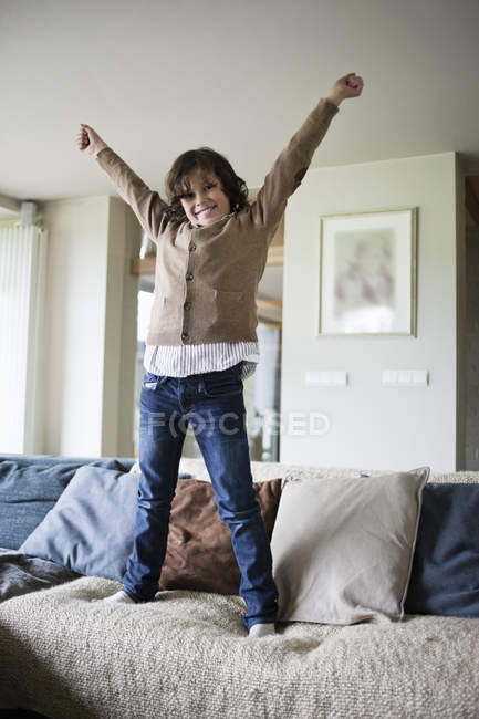 Portrait of cheerful boy standing on sofa with hands up at home — Stock Photo