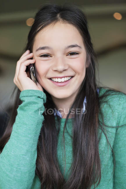Close-up of smiling girl talking on mobile phone and looking away — Stock Photo