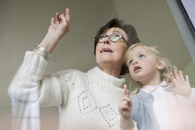 Женщина с маленькой внучкой смотрит в окно — стоковое фото