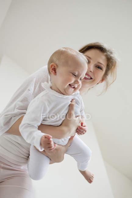 Веселая молодая женщина, играющая с улыбчивой дочкой — стоковое фото