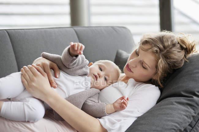 Розслабленої молоду жінку, лежачи на дивані з baby дочка — стокове фото