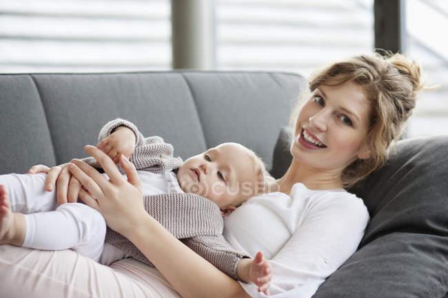 Sonriente joven mujer descansando en sofá con bebé hija - foto de stock