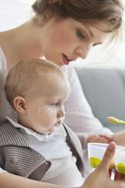 Крупным планом женщины, кормящей вдумчивую дочку — стоковое фото