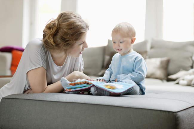 Женщина показывает книгу с картинками дочери на диване дома — стоковое фото
