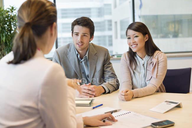 Бизнес-руководитель обсуждает с клиентами в офисе — стоковое фото