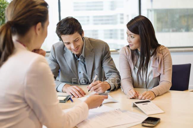 Pareja firmando documentos con ejecutivo de negocios - foto de stock