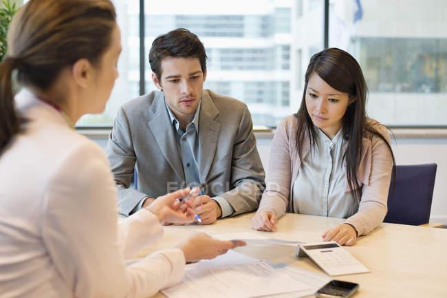 Ejecutivo de negocios discutiendo con clientes en la oficina - foto de stock