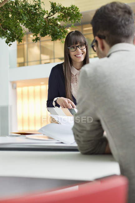 Fashion designers discussing color swatches in office — Stock Photo