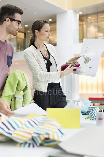Fashion designers working in office with sketches — Stock Photo