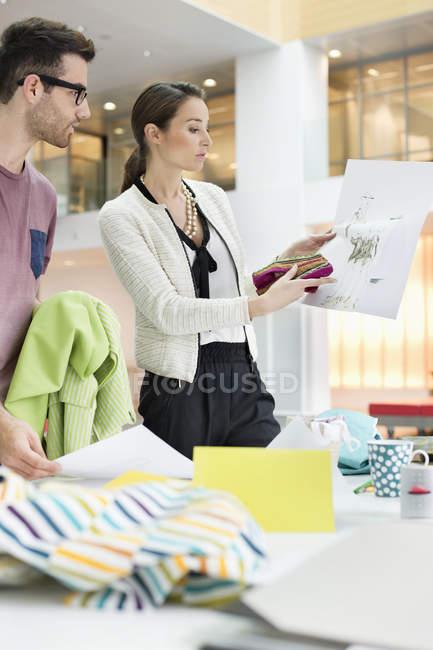 Modedesigner arbeiten im Büro mit Skizzen — Stockfoto