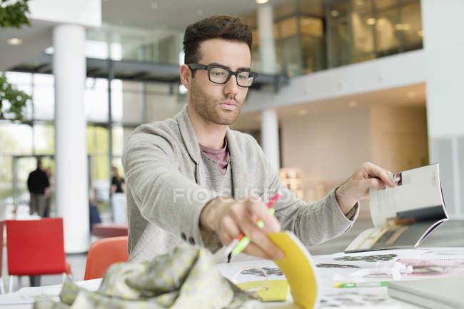 Retrato del diseñador de moda masculino que trabaja en la oficina - foto de stock