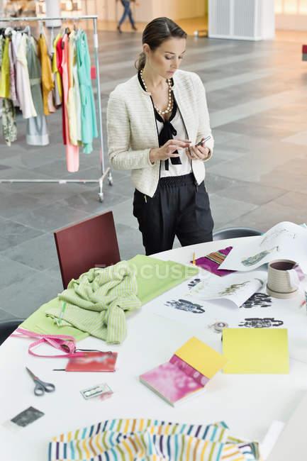 Female fashion designer using mobile phone in office — Stock Photo