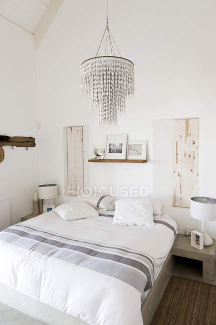 Interior of modern stylish bedroom with elegant chandelier — Stock Photo