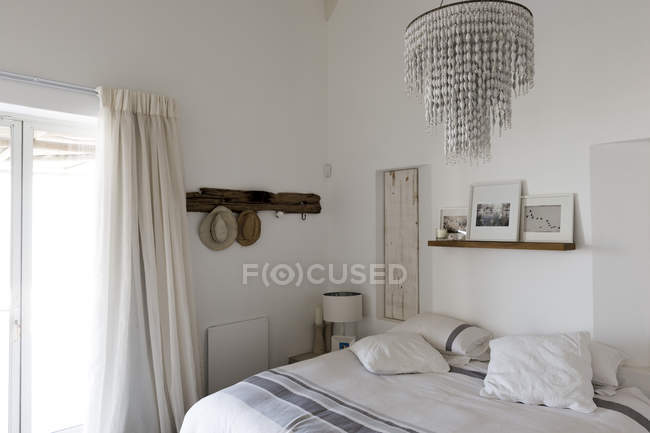 Interior of modern stylish bedroom with elegant chandelier — Stock Photo