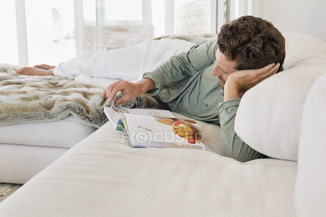 Man lying on bed and reading magazine — Stock Photo