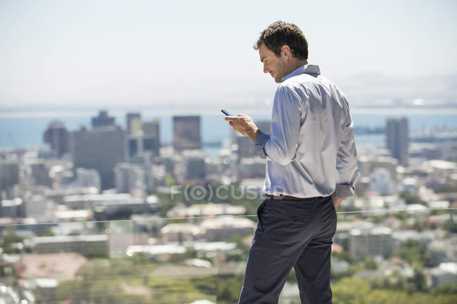 Man standing on terrace in city and using mobile phone — Stock Photo