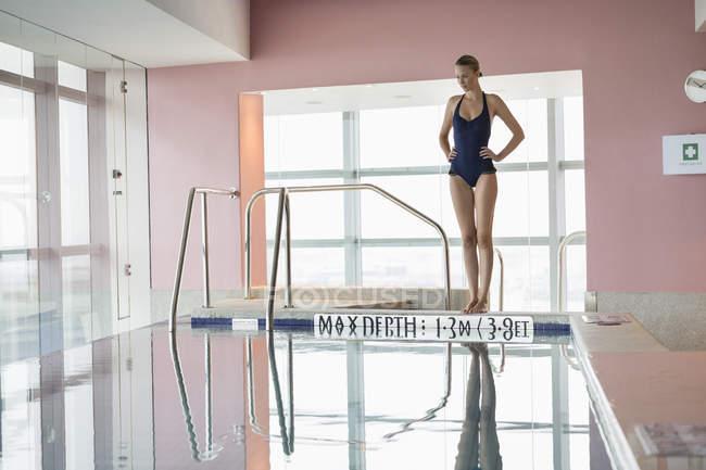 Donna in costume da bagno piedi a bordo piscina con le mani sui fianchi — Foto stock