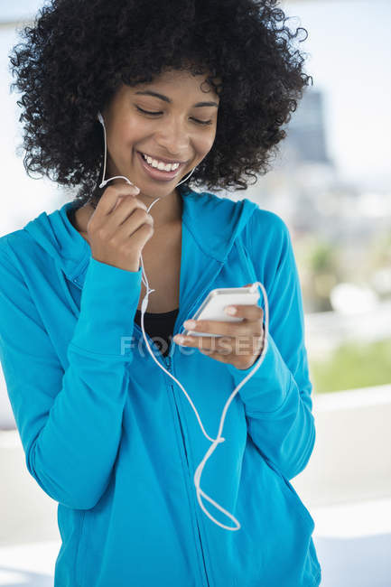 Smiling woman listening to music with mobile phone and earphones — Stock Photo