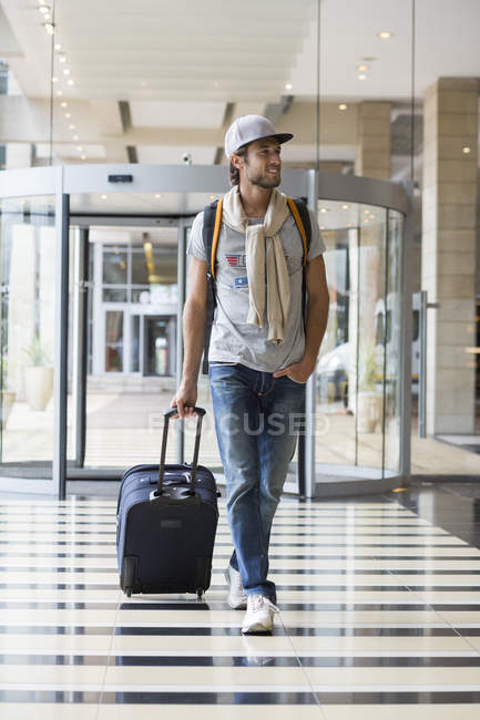 Young smiling man pulling luggage at airport — Stock Photo