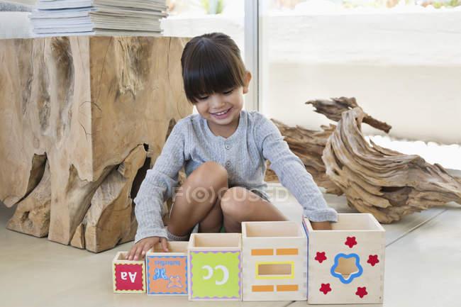 Милая маленькая девочка играет с вложенными кубиками дома — стоковое фото