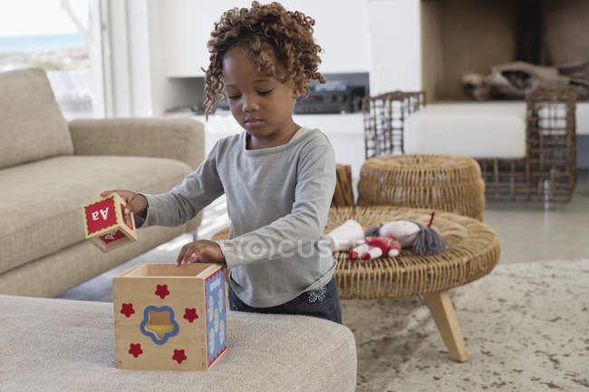 Little girl playing with toys on sofa at home — Stock Photo