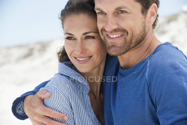 Close-up de casal romântico feliz abraçando na praia — Fotografia de Stock