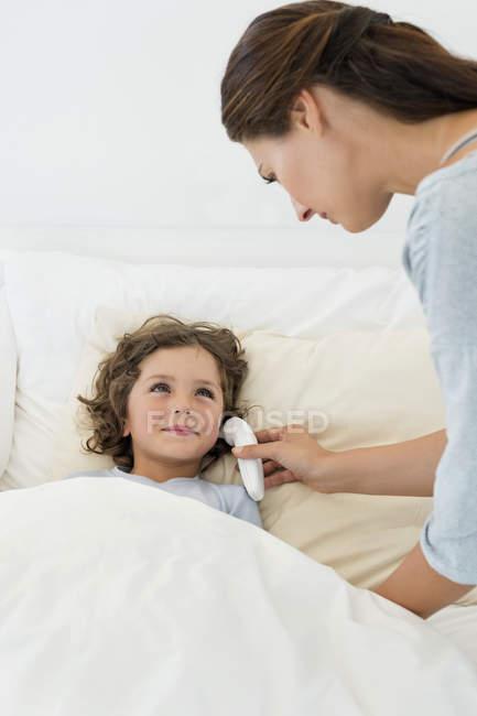 Donna che controlla la febbre del figlio con termometro — Foto stock