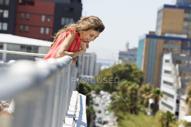 Smiling woman looking down from terrace of building in city — Stock Photo