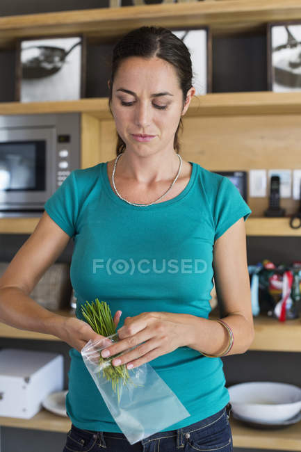 Woman packing herbs for storage in kitchen — Stock Photo