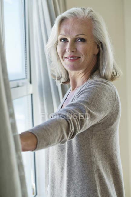 Пожилая женщина, стоящая у окна и смотрящая в камеру — стоковое фото