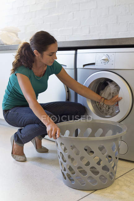 Woman doing laundry with washing machine at home — Stock Photo