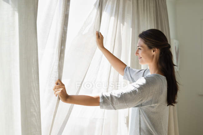 Smiling woman opening curtain of window at home — Stock Photo