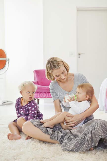 Woman feeding milk baby with bottle on white furry carpet — Stock Photo