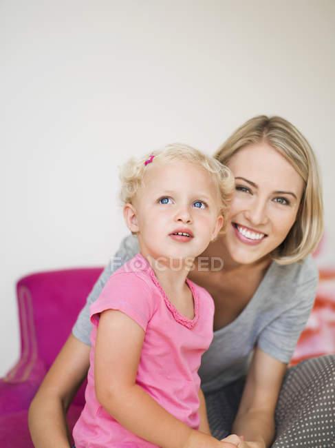 Усміхається жінка сидить з Симпатичні блондин дочка вдома — стокове фото