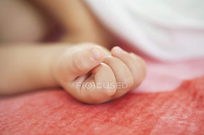 Primo piano della mano del bambino che dorme a letto su sfondo sfocato — Foto stock