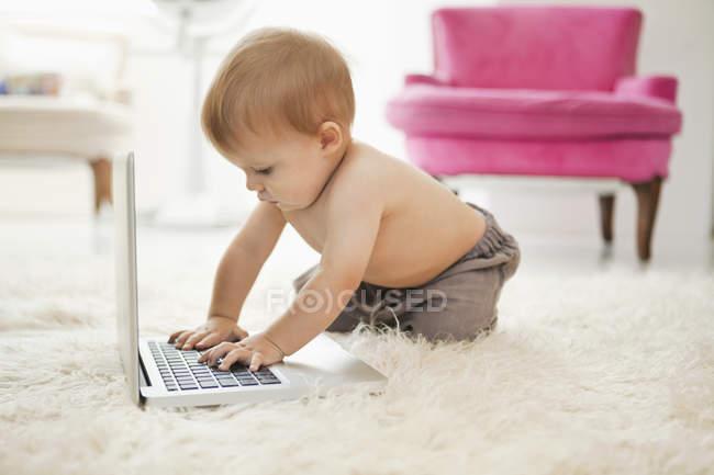 Сорочки хлопчик грає з ноутбуком на білий пухнастий килим — стокове фото