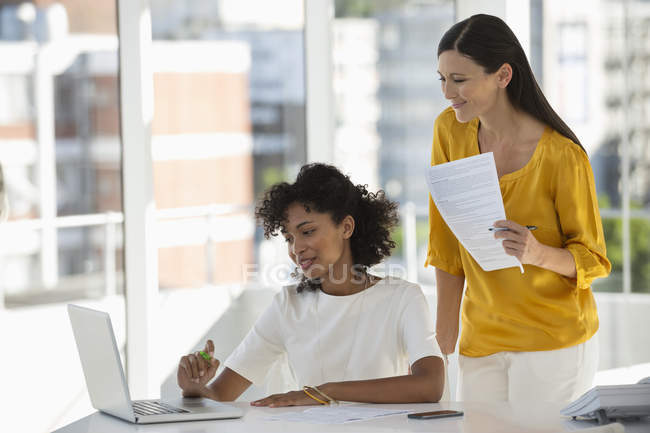 Due donne d'affari che usano su computer portatile a finestra in ufficio — Foto stock