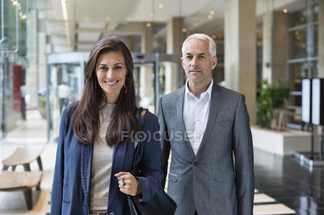 Ritratto di coppia d'affari sorridente in piedi nella hall dell'hotel — Foto stock
