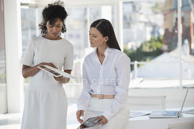 Interior designer showing color swatches to woman in office — Stock Photo
