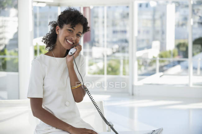 Portrait of smiling woman talking on landline phone in office — Stock Photo