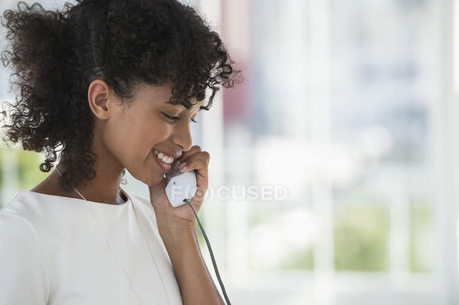 Smiling woman talking on landline phone — Stock Photo