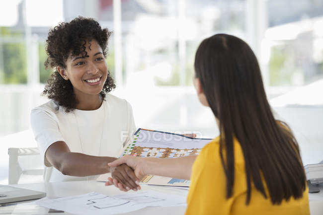 Real estate agent shaking hands with woman in office — Stock Photo