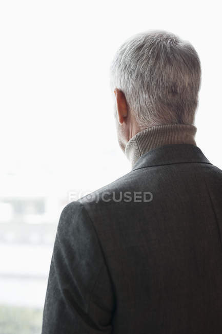 Thoughtful mature man looking through window — Stock Photo