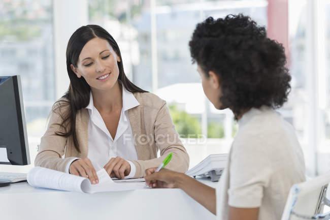 Mulheres de negócios que trabalham no escritório, documento de assinatura da mulher no escritório — Fotografia de Stock