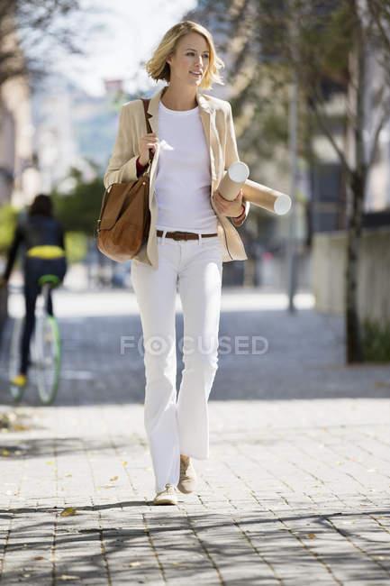 Architecte femme marchant dans la rue avec des rouleaux de papier — Photo de stock