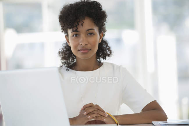 Portrait of woman sitting in front of laptop in office — Stock Photo