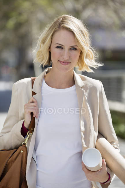 Portrait of female architect carrying paper rolls — Stock Photo