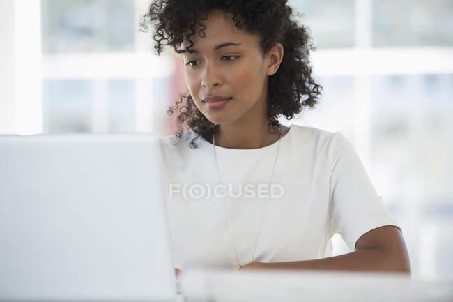 Сфокусированная женщина работает на ноутбуке в офисе — стоковое фото