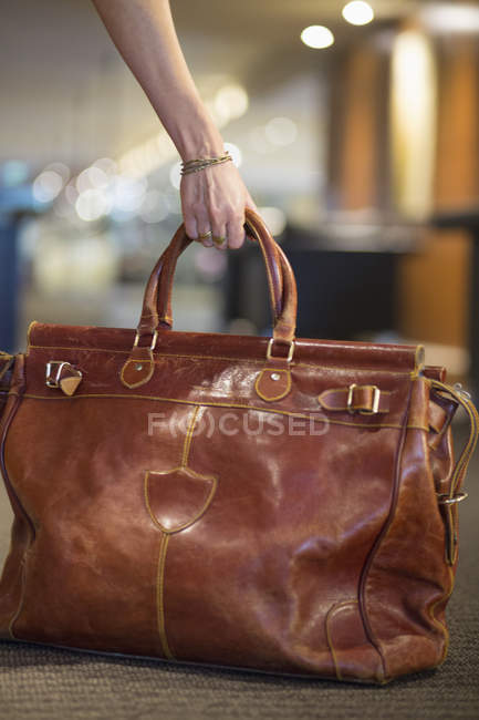 Close-up of female hand picking up travel leather purse — Stock Photo