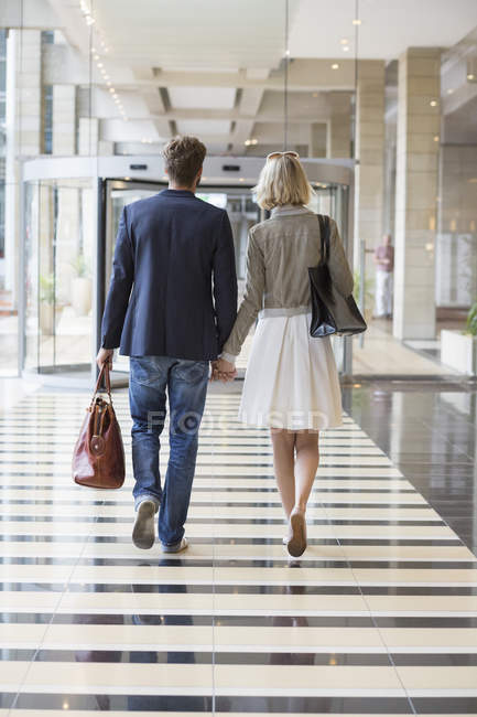 Elegant couple walking at airport holding hands — Stock Photo